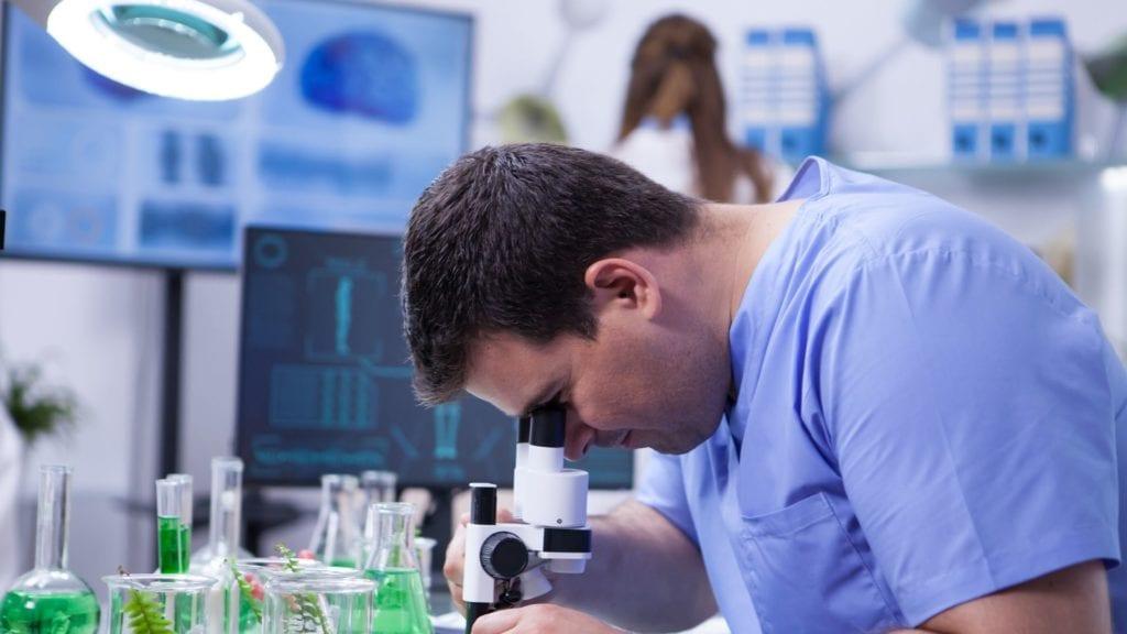חוקר השפעות של שמן קוקוס על שיער בודק שיער במיקרוסקופ
