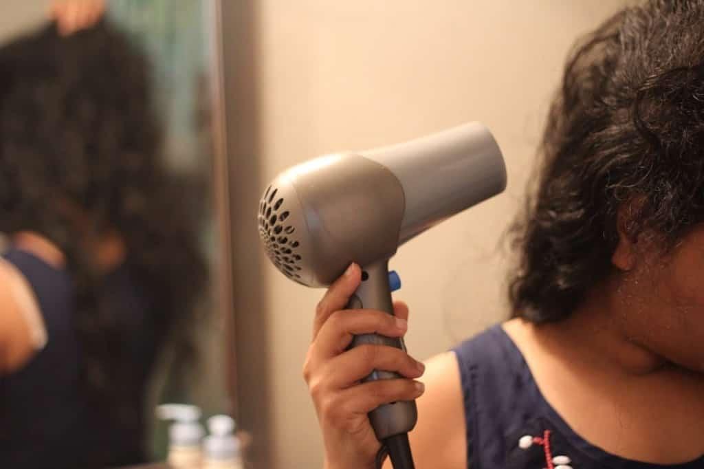 אישה מייבשת שיער עם פן