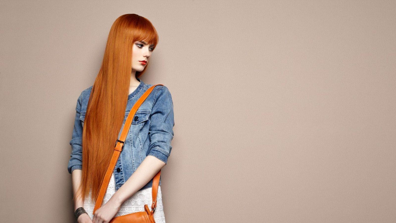 תמונה של אישה עם שיער ג'ינג'י ארוך מאוד וחלק שמפנה לדף תכשירי השיער לשיקום של מילר
